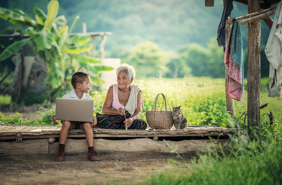 Young child showing his grandma what's on his laptop - online influencer
